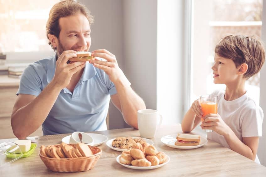 Imagem de pai e filho tomando café da tarde.
