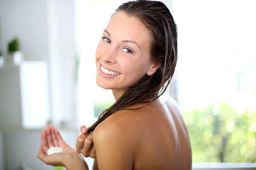 Mulher com condicionador na mão