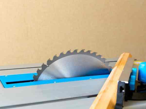 Imagem de serra elétrica com madeira ao lado.