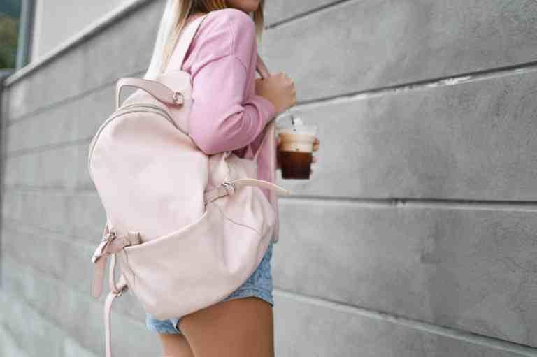 Mulher com mochila rosa.