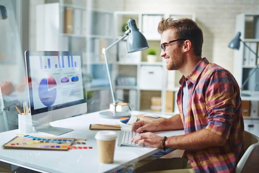 Homem trabalha em sua mesa em um computador com um teclado sem fio