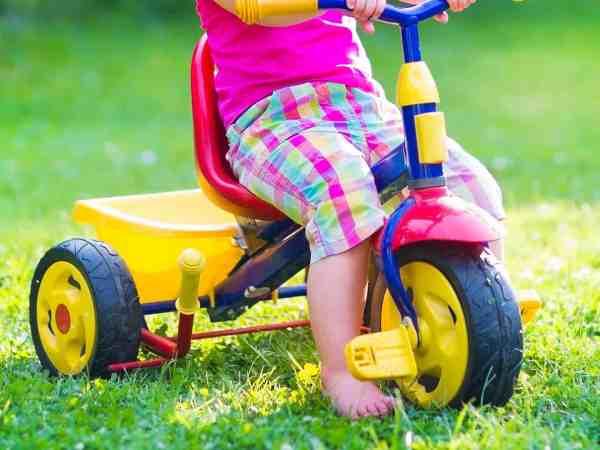 Imagem de criança em triciclo infantil.