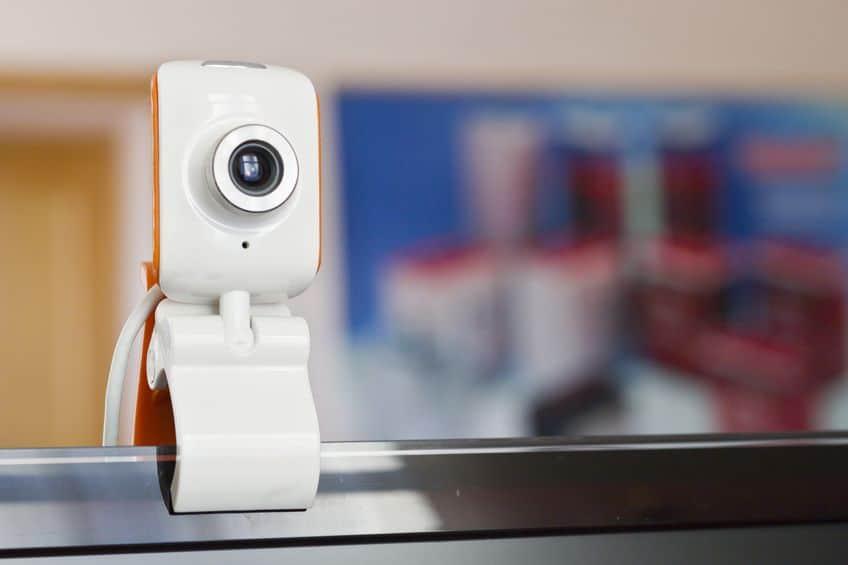 Imagem destaca uma webcam fixada na tela de um computador com o auxílio de um suporte
