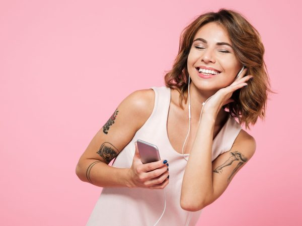 girl listen music on a pink background