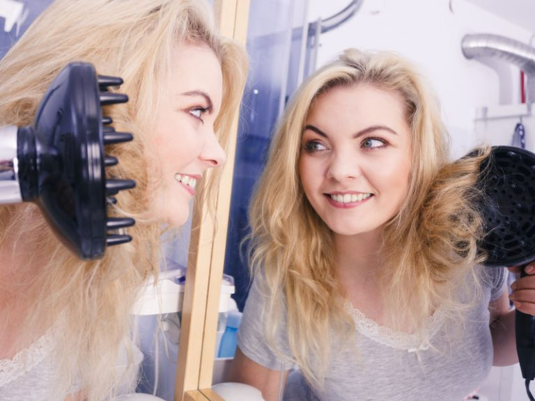 blonde girl looking at her in the mirror