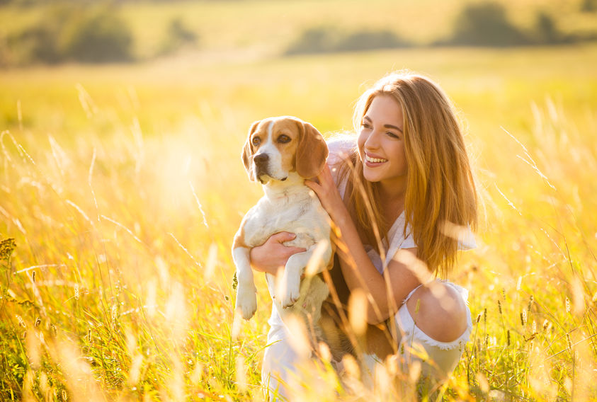 cute girl with a dog on a open field