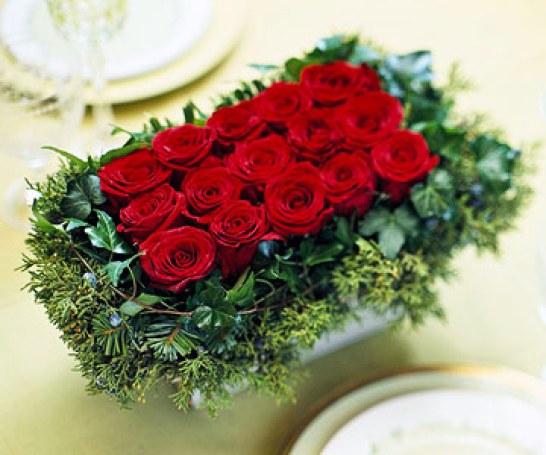 Questo centrotavola, elegante e suggestivo, è realizzato con 15 rose rosse disposte a rettangolo all'interno di un contenitore della stessa forma
