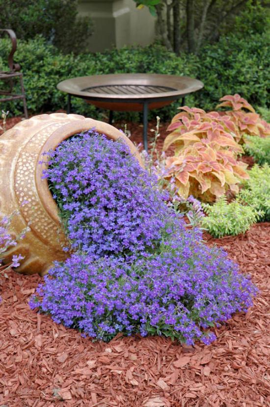 enorme vaso, nello specifico un'anfora, adagiato a terra come fosse caduto, dalla cui apertura fuoriesce, sparpagliandosi nel prato circostante, una cascata di piccoli fiori
