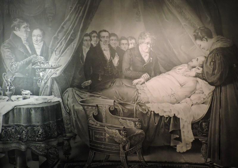 """Museo Farmacia Militar - """"La enfermedad de Fernando VII"""", de Federico Madrazo. A la izquierda se puede ver a Agustín José de Mestre, Boticario Mayor, y a Gerónimo Lorenzo, primer boticario de cámara, que lleva la bandeja con las medicinas."""