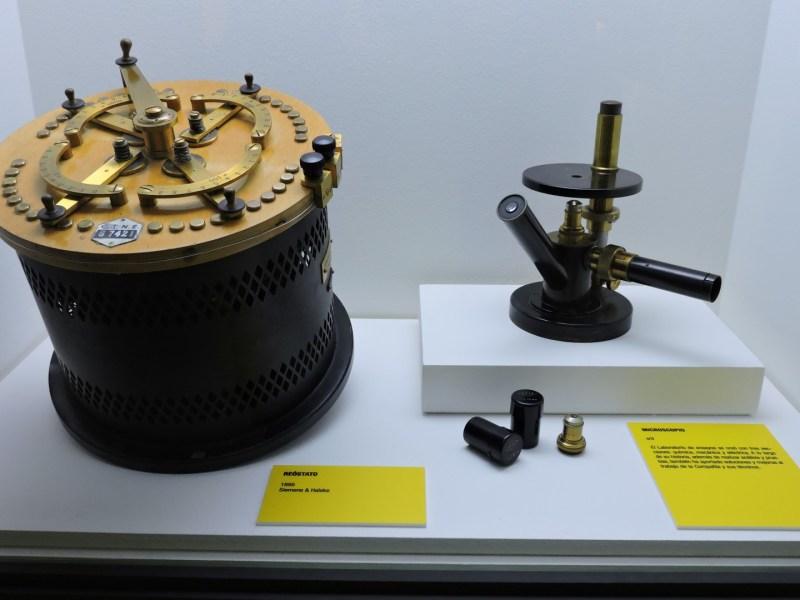 Museo de las Telecomunicaciones - Un reostato (potenciómetro antiguo) que permite variar la resistencia de un circuito. A la derecha un microscopio antiguo