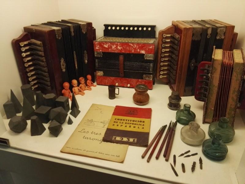 Museo del Acordeón - Vitrina con objetos escolares de los años 30, incluyendo varios acordeones.