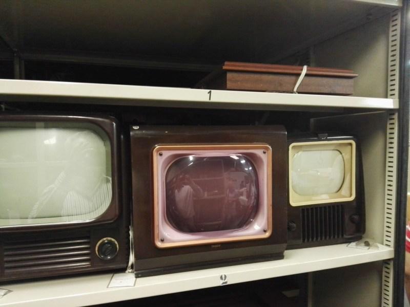 Almacén del MUNCYT - Diversos televisores antiguos. En medio un Philco con la pantalla rosa.