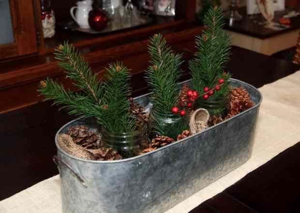 idea natalizia che si può facilmente realizzare riempendo un vaso da fiori con barattoli che contengono ramoscelli di pino, bacche, vischio e pigne