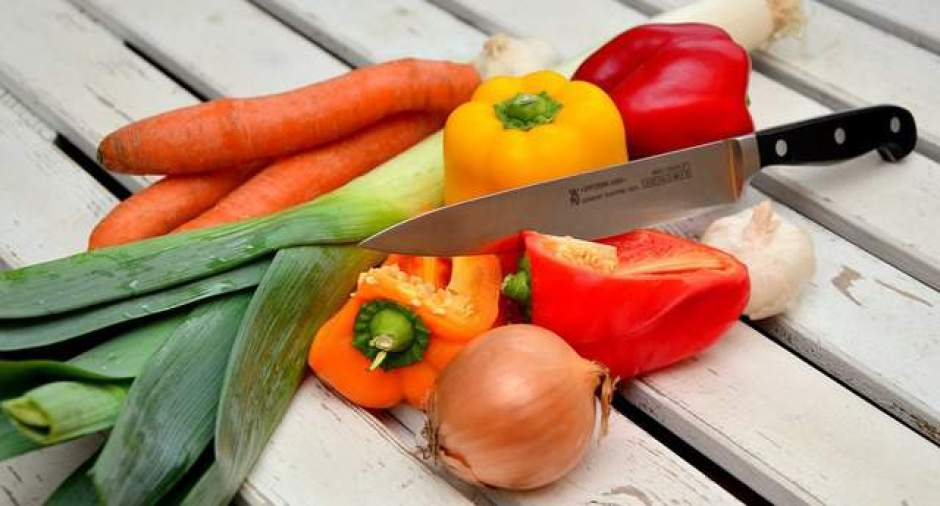 Tagliere con peperoni, carote, aglio, cipolla e porri.