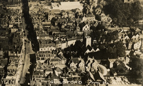 Can you identify any buildings in this aerial view of Guildford from about the 1920s or 30s?