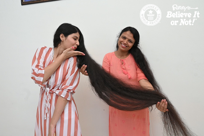 Nilanshi blowing a kiss to her hair while her mum holds it up