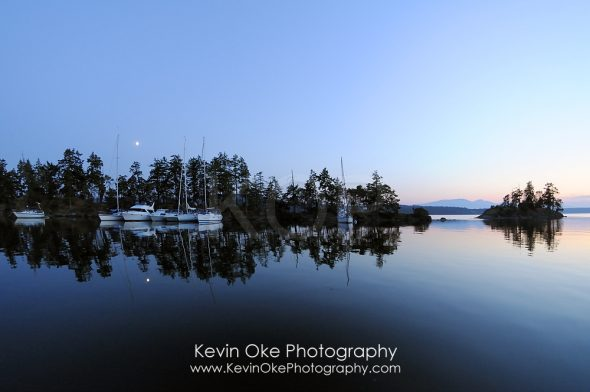 Moonrise over calm waters and boats in Princess Bay, Wallace Island, Gulf Islands, British Columbia, Canada