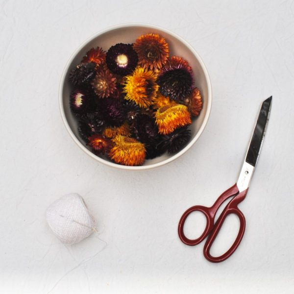 A bowl filled with paper daisies, a pair of scissors, a needle in string