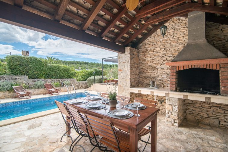 Outside dining area with BBQ under traditional stone roof