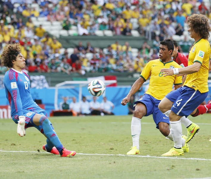 Mexico's Ochoa makes a save in front of Brazil's Paulinho, Luiz and Fred during their 2014 World Cup Group A soccer match at the Castelao arena in Fortaleza