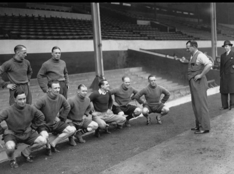 Tom Whittaker talking to Fred Perry and some of the Arsenal players