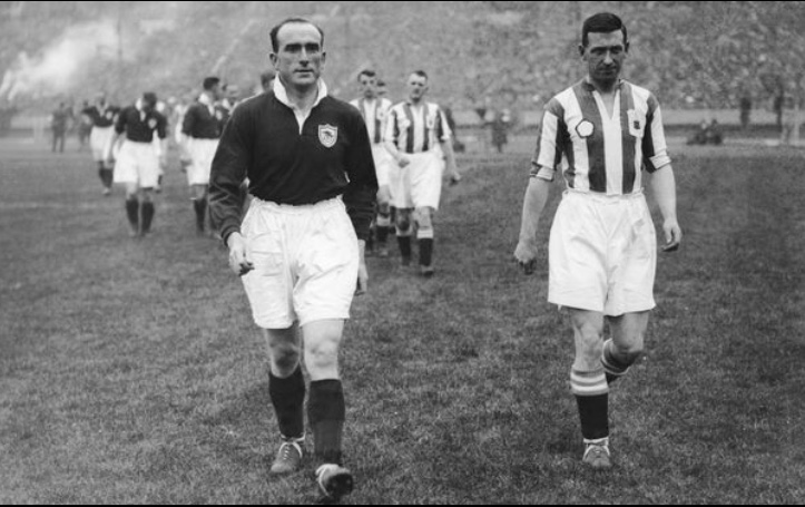 Tom Parker and Tom Wilson lead the Arsenal and Huddersfield Town teams out side by side at the 1930 FA Cup Final. A suggestion by Herbert Chapman. A tradition which is still observed to this day