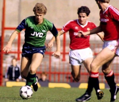 Woodcock takes on a couple of Man Utd players wearing the green and blue Arsenal kit