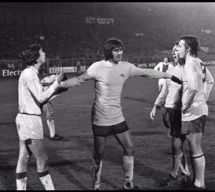 Johan Cruyff doesn't see eye to eye with John Radford and Charlie George in Amsterdam in the first leg