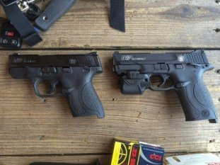 The new M&P22 Compact is shown here (right) next to a Smith & Wesson Shield (left). I put a Crimson Trace Rail Master laser on my test gun because... Fun!
