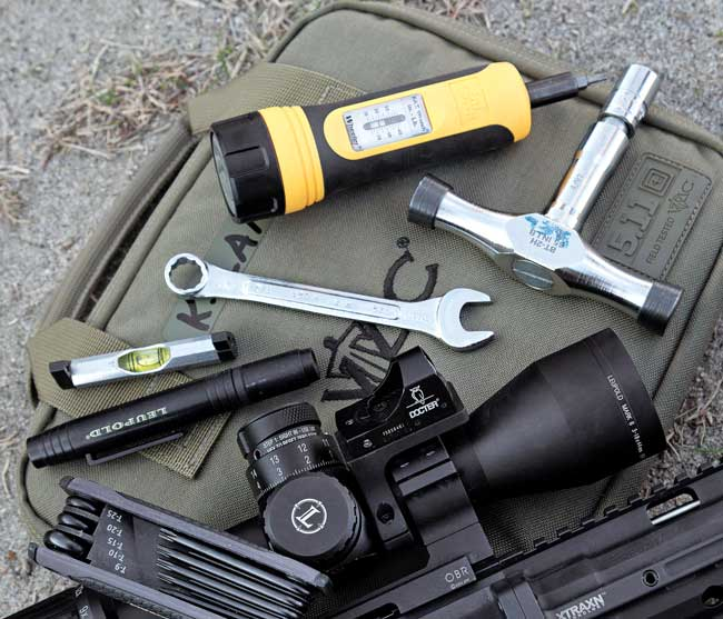 Tools of the modern sniper rifle, clockwise  from bottom left: Torx wrench set, Leupold lens pen, small level, half-inch wrench for detaching rings from base, T-handle with 65 inch-pounds torque wrench and Wheeler's FAT adjustable torque driver with bits.