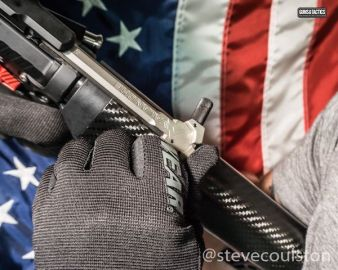 gloved hand with avalanche charging handle and american flag background