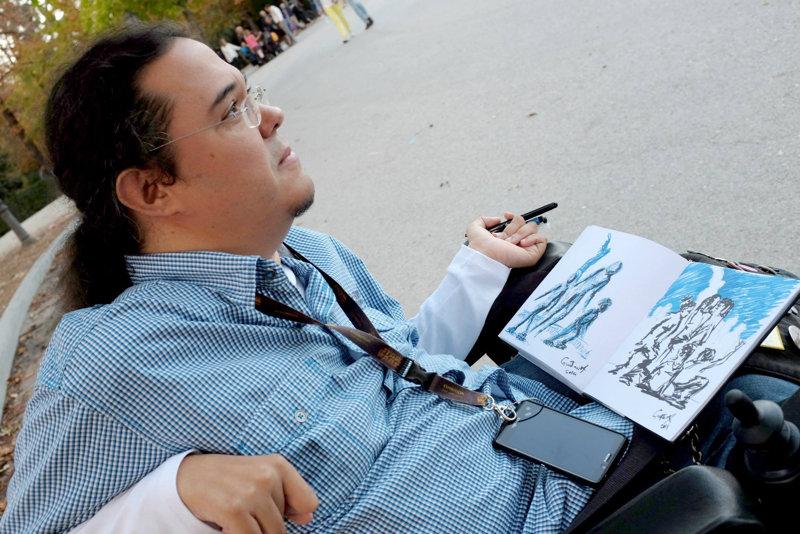 Foto de Gustavo Adolfo Díaz G. con el cuaderno de dibujo y un pincel en la mano