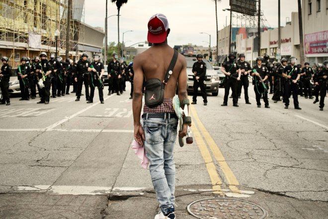 Junger Mann bei Protesten in Los Angeles mit freien Oberkörper in Rückenansicht blickt auf Gruppe von Polizisten. Aufgenommen von Thomas Kretschmann