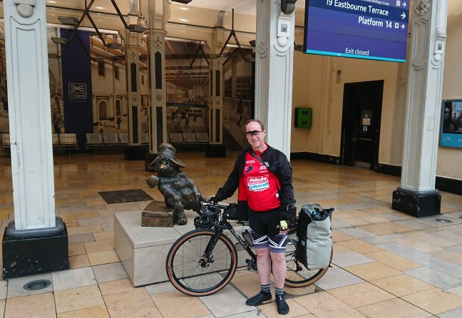 Rider with bike in front of Paddington Bear statue, Paddington Station