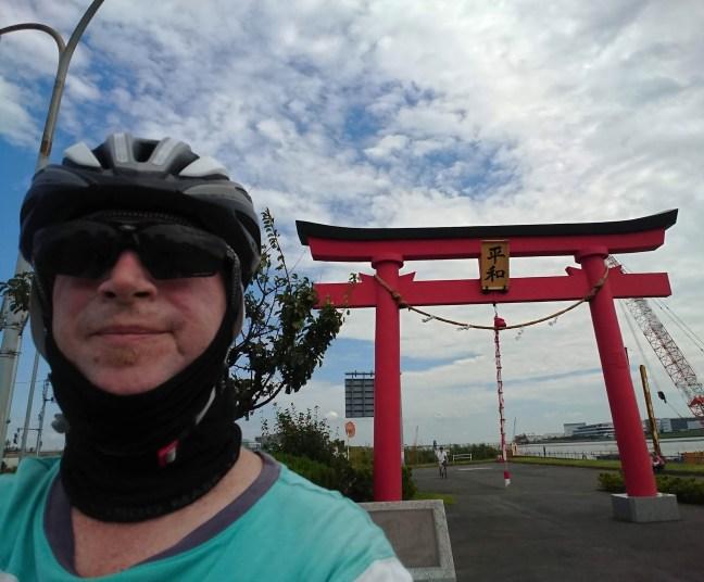 Selfie of biker in helmet and shades in front of red torii