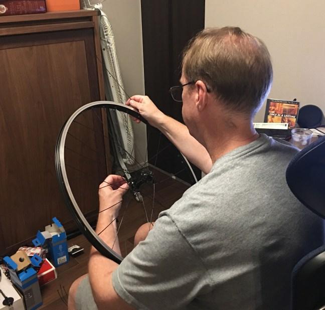 Man lacing a bicycle wheel
