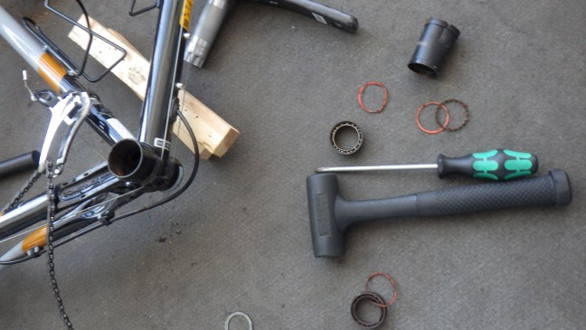 Remains of bottom bracket strewn on floor with tools