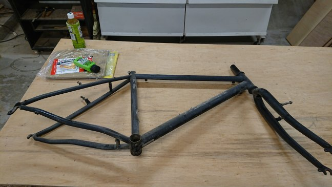 Bike frame, sandpaper, chemicals and green tea on a wooden work table