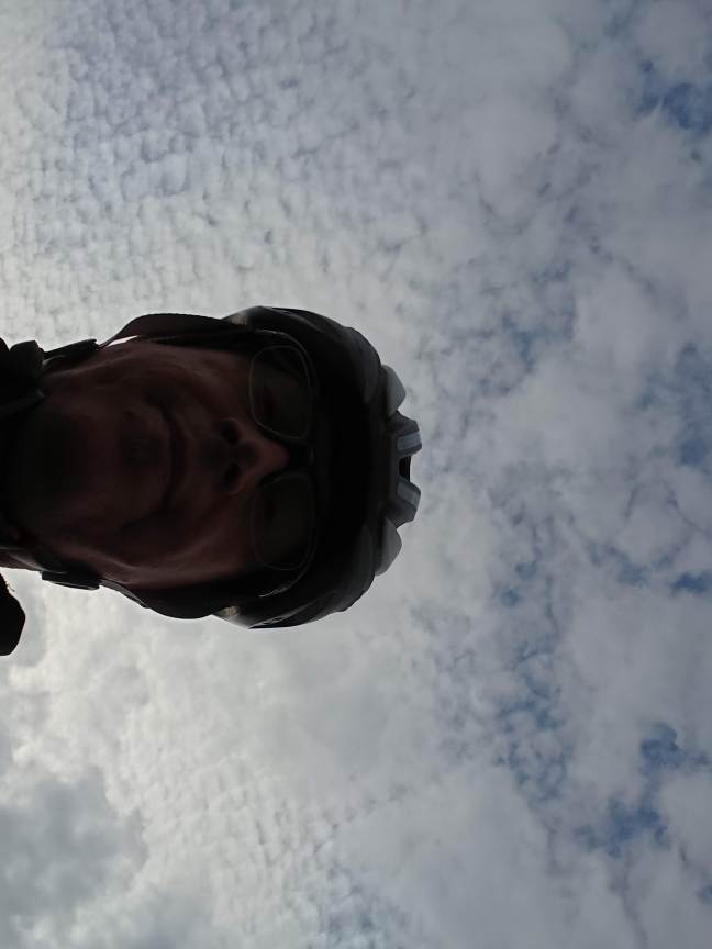 Selfie of man in cycling helmet silhouetted against a cloudy sky