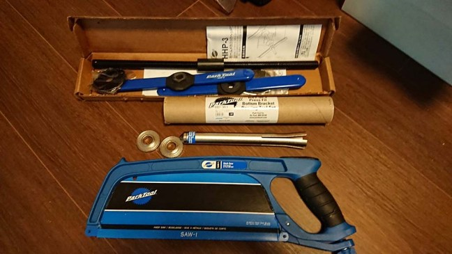 Park Tool bearing press, removal tool and hacksaw on a wood floor