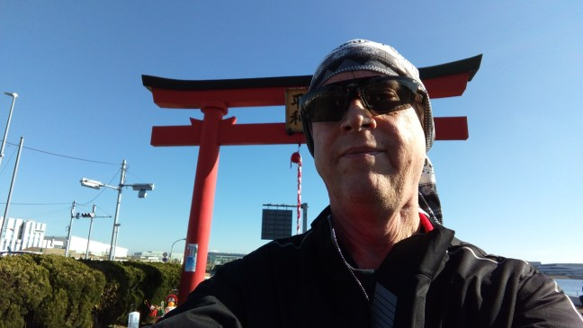 Selfie of biker wearing sunglasses and a bandana in front of a Japanese shrine torii