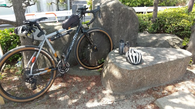 Bicycle, helmet and water bottles on and among decorative rocks in park