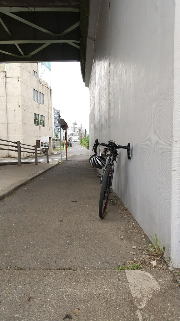 Bicycle leaning against a bridge abutment
