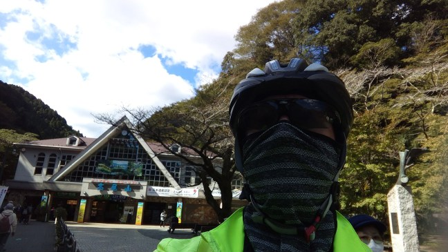 Cyclist selfie (in mask and helmet) in front of Takaosan cable car entrance