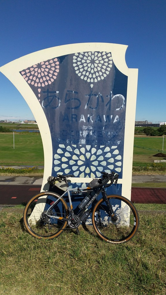 Bicycle leaning against sign for Arakawa