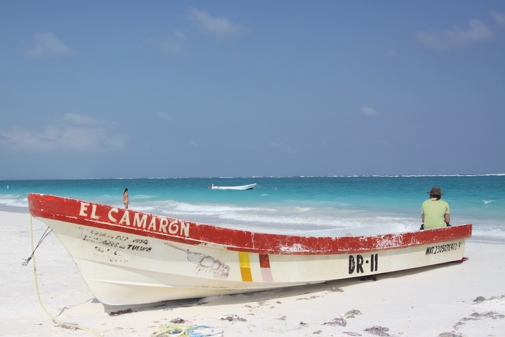white and red fishing boat on a white sandy beach