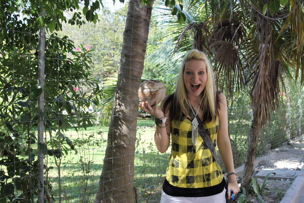 Blond girl holds up coconut with excitement