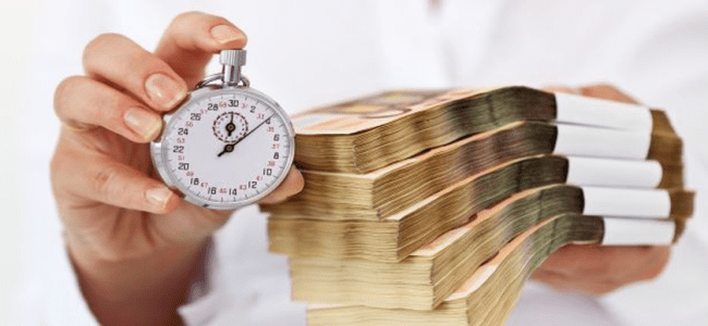 man wearing white polo holding out clock and bundle of money