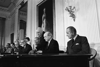 President Lyndon B. Johnson looks on as U.S. Secretary of State Dean Rusk prepares to join foreign ministers from more than 50 other nations in signing the Nuclear Nonproliferation Treaty, July 1, 1968.  Photo courtesy the LBJ Library, Austin, Texas.