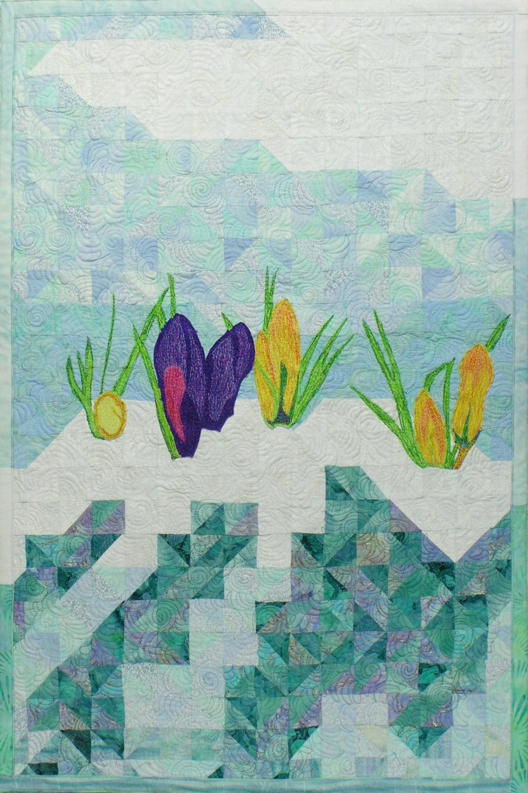 Only the snow surrounding the crocuses is white, otherwise it is in various values of turquoise blue. There are three yellow crocuses marching across the quilt midline, with a single deep purple one acting as a focal point.